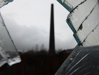 Chatterley Whitfield - The iconic chimney viewed through one of the broken windows of a nearby heapstead (building)