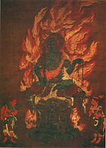 A deity with blue skin color seated on a pedestal and surrounded by flames. Two smaller figures are standing in the lower left and right corners.