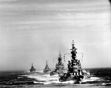 Black and white photo of four warships sailing together
