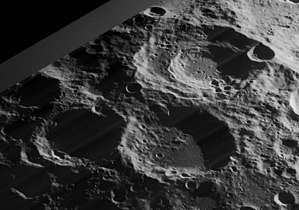 Boussingault (crater) - Oblique view of craters Boussingault (above right), Helmholtz (below right), and Neumayer (below left, mostly in shadow), facing southwest, from Lunar Orbiter 4