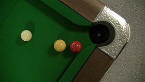Billiard table - A WEPF-style pool table, showing a cue ball and red and yellow balls close to the small, rounded, nearly parallel-sided pocket.