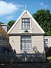 foto van Houten huis met in de topgevel een vensteromlijsting