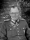 A man wearing a military uniform and glasses with an Iron Cross displayed at the front of his uniform collar.