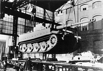 "Tiger at the Henschel plant is loaded onto a special rail car. The outer road wheels have been removed and narrow tracks put in place to decrease vehicle width, allowing it to fit within the loading gauge of the German rail network. Bundesarchiv Bild 146-1972-064-61, Kassel, Verladen eines Panzer VI ""Tiger I"".jpg"