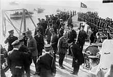 Several men in military uniforms, some wearing the Turkish Fez, aboard a warship; a large, boxy gun turret is on the right.