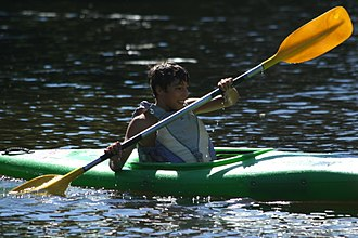 Kayak - Child using oversized equipment. The kayak is floating too high, it is too wide for his hips and shoulders, and it is so deep that his elbows hit the deck. His paddle is also too long. It is impossible for him to paddle efficiently, and he will tire quickly. His PFD is also large enough to slip off over his head while fastened.