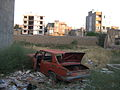 Destroyed red car in a abandoned zone nearnear amin eslami garden- Nishapur 5.JPG