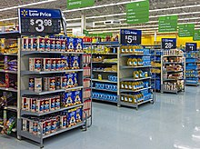 Aisles in a supermarket with small sets of shelves on the end, receding from left to right. Atop each set of shelves is a large white on black sign with the price of an item for sale on those shelves. White on green signs with the types of products in the aisles hang from the high ceiling.