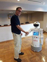 A man is shaking hands with a robot