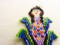 Flat beads used to create an earring, showing a huichol woman and corn.jpg