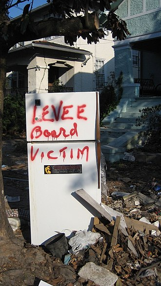 """Orleans Levee Board - Debris set on curb from flood-damaged Uptown home includes trashed """"Katrina refrigerator"""" with graffiti labeling it as a """"levee board victim."""""""