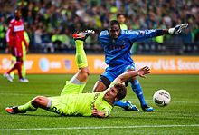 A player in a blue goalkeeper uniform stands with his hands extended over a player in a yellow uniform sliding on the ground. A ball is bouncing away from the players.