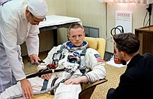 Armstrong, with short hair, partially reclining on a beige chair. He looks very serious. He is wearing a white space suit without a helmet or gloves. It has the U.S. flag on the left shoulder. Two hoses are attached. A technician dressed all in white is bending over him. A dark-haired, darkly dressed man has his back to us. He may be talking to Armstrong.