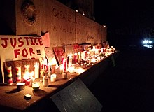 "George Floyd–related and Black Lives Matter–themed protest signs and lit candles placed on the base of the Astoria Park War Memorial; the visible portion of the memorial's inscription reads: ""GREATER LOVE HATH NO MAN THAN THIS THAT A MAN LAY DOWN HIS LIFE FOR HIS FRIENDS ERECTED 1926 BY THE PEOPLE OF LONG ISLAND CITY"" In the background the glaring headlights of a police cruiser."