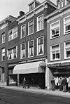 foto van Pand met bakstenen gevel met rechts kroonlijst consoles met leeuwenmaskers, moderne winkelpui