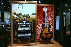 Maybelle Carter - Carter's Gibson guitar, accompanied by a photograph of Carter at the Country Music Hall of Fame