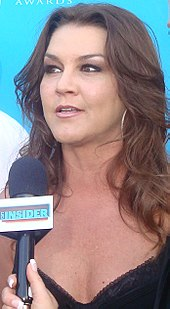 A woman with long dark hair talking into a microphone