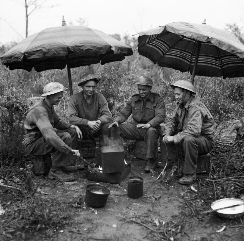 Gunners of 78th Field Regiment, Royal Artillery make use of 'liberated' sunshades to keep the rain off while making a brew, Anzio, Italy, 27 February 1944. NA12275