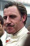 Graham Hill in white racing overalls and looking to the right of the camera