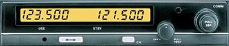 Airband - A typical aircraft VHF radio. The display shows an active frequency of 123.5 MHz and a standby frequency of 121.5 MHz. The two are exchanged using the button marked with a double-headed arrow. The tuning control on the right only affects the standby frequency.