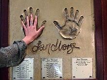plateau mural avec les empreintes de mains de Thorpe, sous lesquelles figurent des plaquettes avec son palmarès.