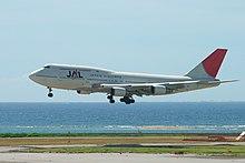 Pesawat Boeing 747-400D sedang mendarat dengan pemandangan taxiway di latar depan dan pemandangan langit dan laut di latar belakang