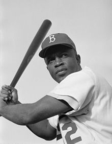 Waist-up portrait of black batter in his mid-thirties, in Brooklyn Dodgers uniform number 42, at end of swing with bat over left shoulder, looking at where a hit ball would be