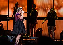 Kelly Clarkson performing in a dark purple dress against an orange-lit LED screen background