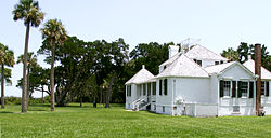 Color photo of the owner's house from a diagonal view, showing a large white structure with black shutters, two gabled pavilions separated by a porch, a taller larger gable in the center, a small gable roof to the right of the closest pavilion, and a partially obscured pavilion with a gabled roof and chimney. A lawn and bent oak and palm trees surround the house