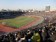 A packed oval shaped stadium with an athletics track. An urban skyline is seen in the horizon and the sky is blue with a few clouds.