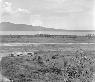 Battle of Ambon - Laha airfield, Ambon (as seen in 1945). The Bay of Ambon and the Laitimor Peninsula are in the background. (Photographer: Staff Sergeant R. L. Stewart.)