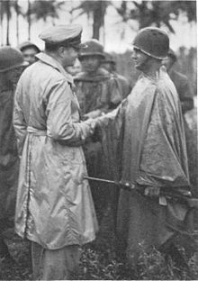 Officer in raincoat shakes hand of soldier wearing steel helmet and waterproof poncho while other similarly attired soldiers look on.