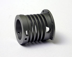Spring (device) - A machined spring incorporates several features into one piece of bar stock