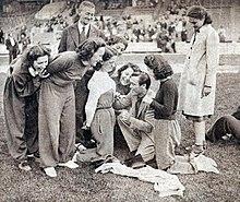 Agenouillé au sol, entouré de femme, un homme écrit sur les vêtements de l'une d'entre elles avec un stylo.