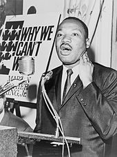 A black and white photograph of Martin Luther King Jr. speaking at a podium with an enlarged cardboard cover of his book Why We Can't Wait in the background