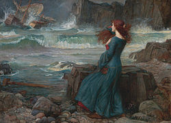 A woman with long reddish hair in a long dark dress, standing on a rocky shore, watching a storm at sea.