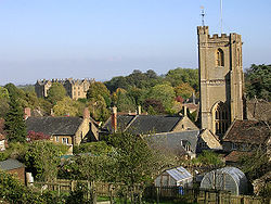 View of the roofs of houses with a prominent square church tower, interspersed with trees.