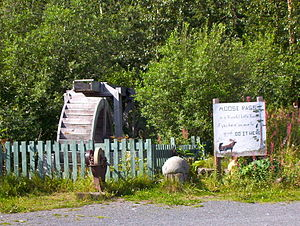 """Moose Pass, Alaska - Water wheel and grindstone by side of Seward Highway. The sign reads: """"Moose Pass is a peaceful little town, if you have an axe to grind, do it here."""""""