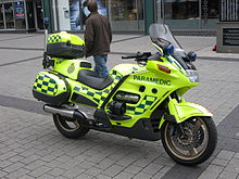 Yellow motorcycle with green battenberg livery parked without rider on a pavement