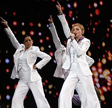 Madonna and her backup singers in white suits, with her right hand stretched up.