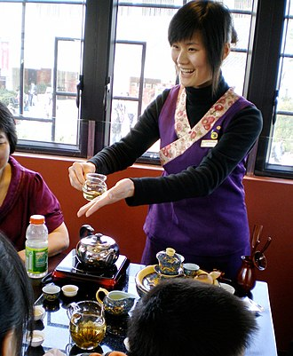 Chinese tea culture - A hostess serves tea at a traditional Chinese tea house.