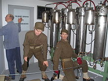 Two saboteurs and a facility employee shown adjacent to the electrolysis chambers.