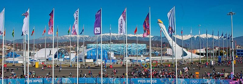 Medals Plaza mit Olympischem Feuer vor dem Hintergrund des Kaukasus