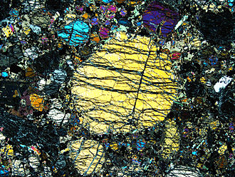 Foidolite - Thin section of foidolite under polarizing microscope. In the foreground there is a large yellow sodium pyroxene grain surrounded by fine grains.