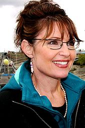 A woman wearing glasses, earrings, red lipstick, a necklace of white beads, and a black jacket on top of a blue hoodie