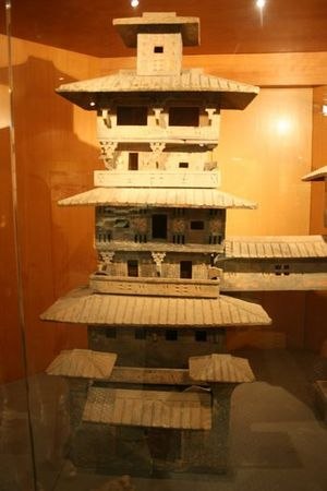 Economy of the Han dynasty - A painted ceramic architectural model—found in a Han tomb—depicting an urban residential tower with verandas, tiled rooftops, dougong support brackets, and a covered bridge extending from the third floor to another tower