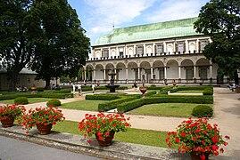 Un bâtiment clair, au toit de cuivre vert, une grande arcade courant face à un jardin fait de pelouse, de buis et de fleurs rouges en pot au premier plan.