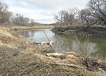 A small river flows through a prairie landscape; brown grasses and leafless trees line the banks.