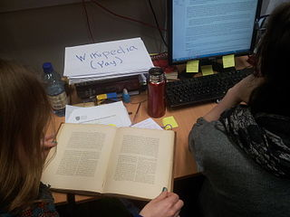 Photo shows a desk with two people sat with an open book. There is a piece of paper upon which is written