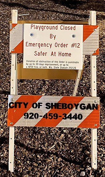 ウィスコンシン州シボイガンの遊び場の看板には、遊び場の設備へのアクセスを閉鎖した理由として、トニーエバーズ知事の自宅滞在命令(「緊急命令#12」と記されています)、および命令違反の刑事上の影響が記されています。 。
